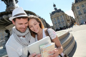 Couple standing by the Place de la Bourse with electronic tablet